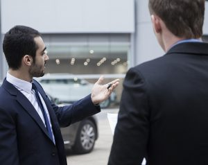 A man in a suit holds a car key and looks towards the cars as he shows another man in a suit