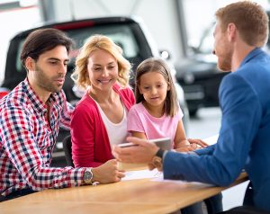 A man in a suit shows a man, woman and child an image on a tablet in a car showroom