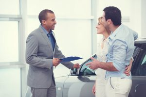 A man and woman embrace as they speak to a salesperson next to a new car