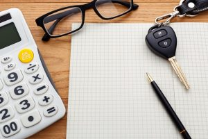 A pen and piece and paper on a desk next to a set of car keys pair of glasses and a calculator
