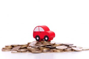 A small wooden red car toy sat on a pile of money