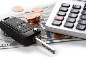 A car key and calculator sat on top of some money with a pile of coins next to them