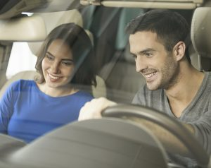 A man and woman smile and look at the dash of their new car