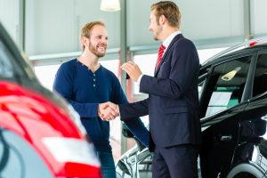 Two men shaking hands besides two cars as a man receives the keys to his car