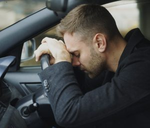 Young man sitting inside car is stressed after being refused car finance
